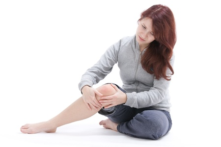 Woman palpate her painful knee Studio shot against white background