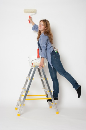 House painter woman standing on stepladder photo