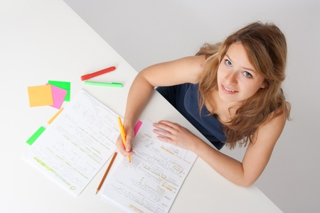 hardworking: College student studying (swot up) for exam. Focused on face. Top view.