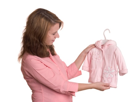 por nascer: Pregnancy concept without showing abdomen - pregnant woman pick clothing for her unborn daughter