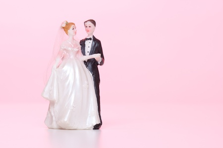 Wedding figurines  bride and groom  on pink background  photo