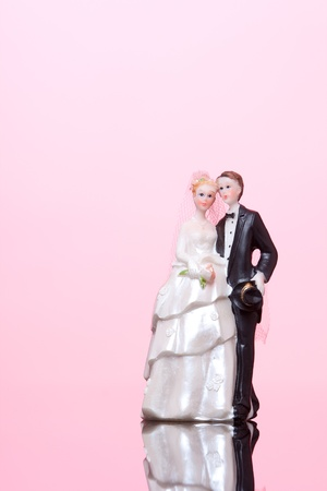 Wedding figurines (bride and groom) on pink background. photo
