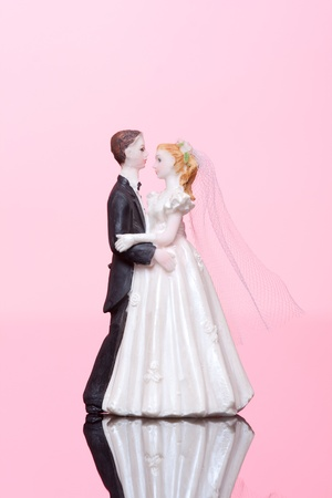 Wedding dancing figurines (bride and groom) on pink background. photo