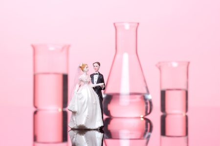 Chemistry of love concept. Wedding cake figurines and laboratory glassware against pink background. photo