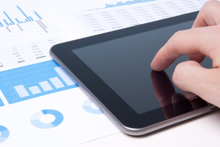 medium close up: Modern business analyst working with digital tablet computer, sheet and graphs