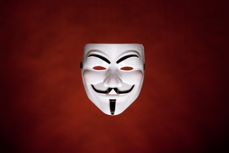 guy fawkes: Studio shot of an Anonymous face mask, known as Guy Fawkes Mask from the movie V for Vendetta on dark red background  Editorial