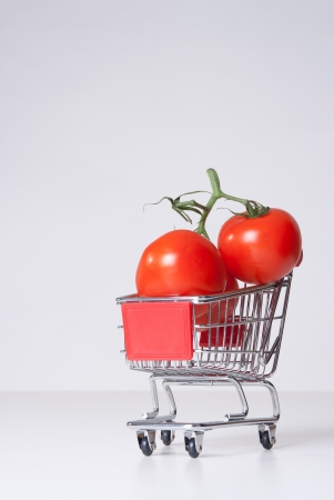 Buy fruit and vegetable concept  could be used for genetically modified food, GM food   Shopping cart  shopping trolley  with big tomatoes  photo