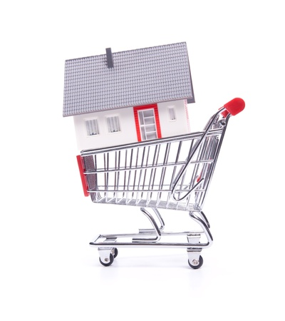 Buy new house concept - model of the house in shopping cart on white background  photo