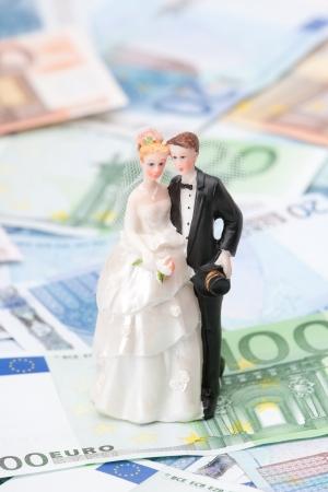 Wedding expense concept - wedding figurines bride and groom and money 版權商用圖片
