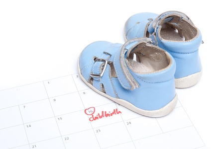 bootee: Handwritten text childbirth as reminder in calendar and baby shoes (bootee).