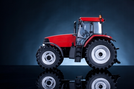 agribusiness: Tractor studio shot on blue background  Side view  Stock Photo