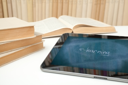 home schooling: E-learning concept  Digital tablet in study room with image of chalk board on touch screen with handwritten text e-learning  Stock Photo