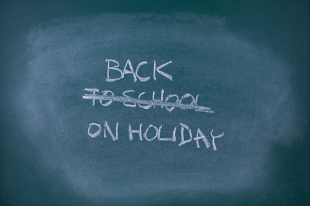 hooray: Back on holiday concept  Writing back to school scored out and replaced with text back on holiday, school chalkboard  blackboard   Stock Photo