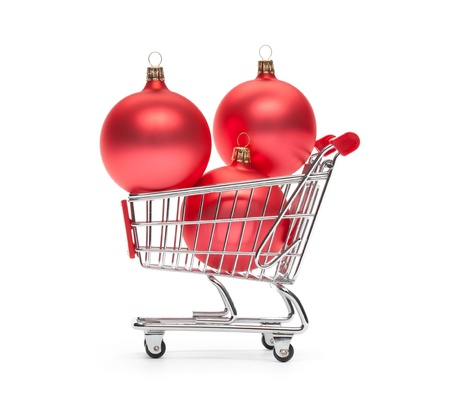 consumerism: Shopping cart with three Christmas decorations on white background, side view  Christmas consumerism  or sale  concept  Stock Photo