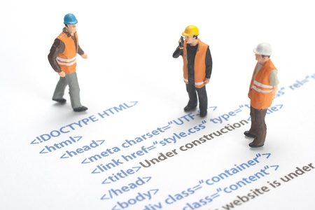 web page under construction: Printed HTML code of website  internet page  under construction  Construction worker figurines working on code