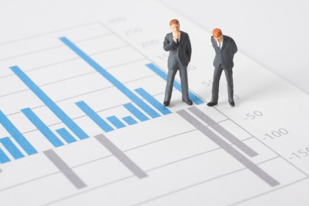 illustrating: Business report, graph and business figurines illustrating profit decrease analyze   Stock Photo