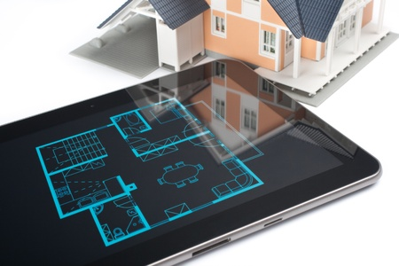 screen shot: Model of the house and digital tablet with interior blueprint  corresponding with model  on screen  Architect Stock Photo