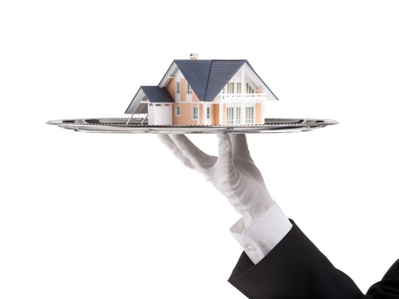 Offer of house concept (real estate). Waiter is having model of the house on tray. Stock Photo