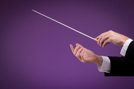 comunicacion no verbal: Hombre manos de orquesta, una con bastón. Fondo púrpura. Foto de archivo