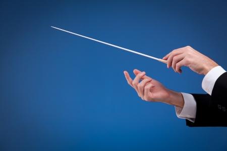 comunicacion no verbal: Hombre manos de orquesta, una con bast�n. Fondo azul.