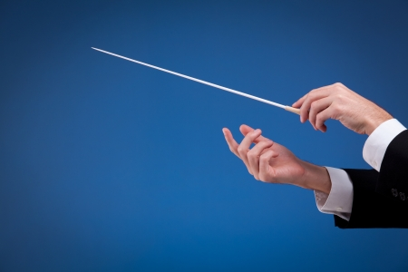 conductor: Male orchestra conductor hands, one with baton. Blue background.
