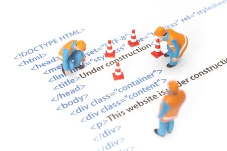 Impreso código HTML de la página web (página de internet) en construcción. Figurines trabajador de la construcción que trabajan en código. Foto de archivo