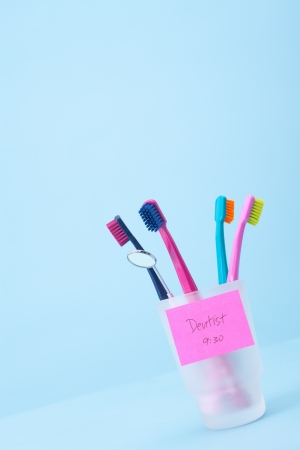 speculum: Dentist visit concept - four toothbrushes, speculum and sticky note reminder  Selective focused on sticky note reminder, blue background  Stock Photo