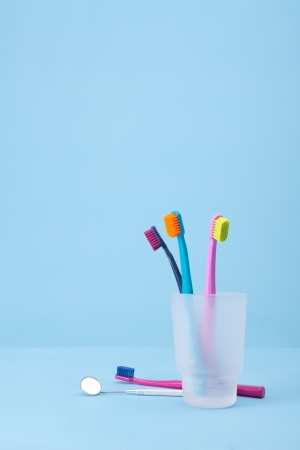 speculum: Four toothbrushes and speculum  dental mirror  - dental hygiene  Selective focused on front toothbrush, blue background