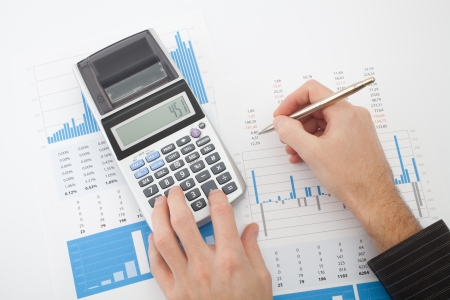 Business analysis - calculator, sheet, graphs  business report  and analyst hand, top view photo