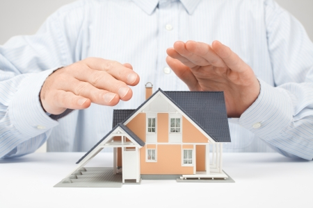 realty residence: Property insurance concept - man protect model of the house. Stock Photo