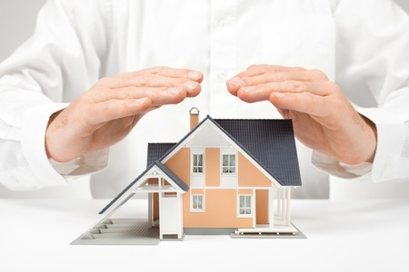 small home: Property insurance concept - man protect model of the house. Stock Photo