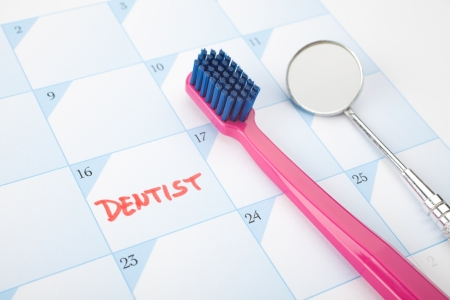dentition: Dont forget visit a dentist concept - toothbrush and speculum on calendar with dentist note. Selective focused on text dentist.