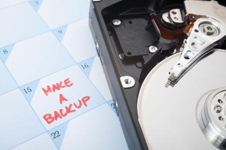 disco duro: Haga una copia de seguridad de disco duro recordatorio. Calendario con el texto y el disco duro. Selectivo centrado en respaldo texto y la cabeza magnética.