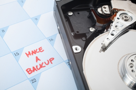 backups: Make a backup of hard disk reminder. Calendar with text and hard drive. Selective focused on text backup and magnetic head.