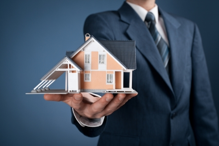 real estate agent: Real estate agent offer house represented by model.  Stock Photo