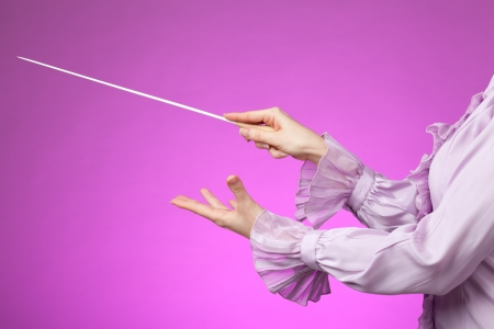 Female orchestra conductor hands, one with baton Pink background