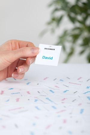 name day: Woman select first name for child  David   First names printed on paper and date of name day  Stock Photo
