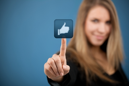 Social media concept. Young woman click on the like button.  Stock Photo