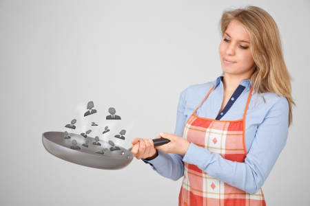 Female human resources officer (recruiter) cook and mix (combine) ideal team in the pan.  photo