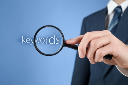 Keywords analysis, look for, search for and seek concept. Man with magnifying glass and text keywords.