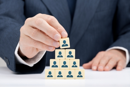 Human resources and corporate hierarchy concept - recruiter complete team by one leader person  CEO  represented by icon