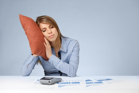 doze: Woman having a rest (sleep, relax, snooze, nap, doze) in work. Burnout tired worker. Weary woman with pillow, graphs, sheets and calculator.