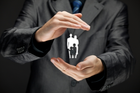 family policy: Family life insurance, family services, family policy and supporting families concepts  Businessman with protective gesture and silhouette representing young family  Stock Photo