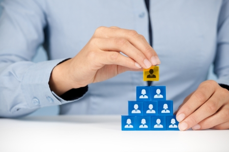 resources: Human resources and corporate hierarchy concept - recruiter complete team by one leader person  CEO  represented by gold cube and icon   Stock Photo
