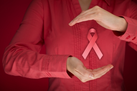 cancer woman: Breast cancer awareness - woman with protective and support gesture and pink ribbon.