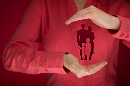 shielding: Family life insurance, family services, protecting family, family policy and supporting families concepts. Woman with protective gesture and silhouette representing young family.  Stock Photo
