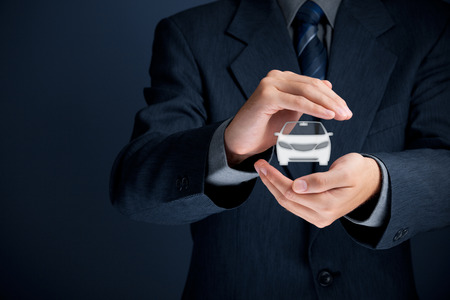 automobile insurance: Businessman with protective gesture and icon of car