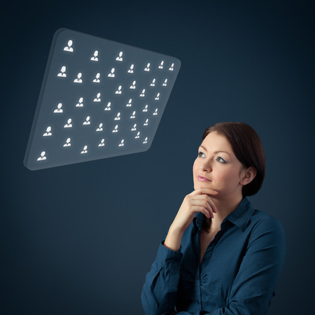 candidates: Human resources female officer think about new candidates or team structure displayed on futuristic virtual screen. Marketing specialist think about customers. Stock Photo