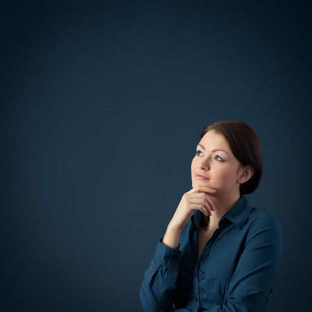 consider: Young woman think (contemplate) about something, blue background. Stock Photo