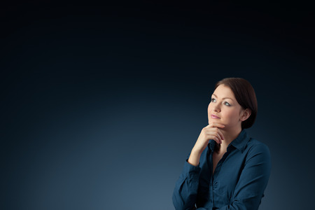 ruminate: Young woman think (contemplate) about something, blue background.